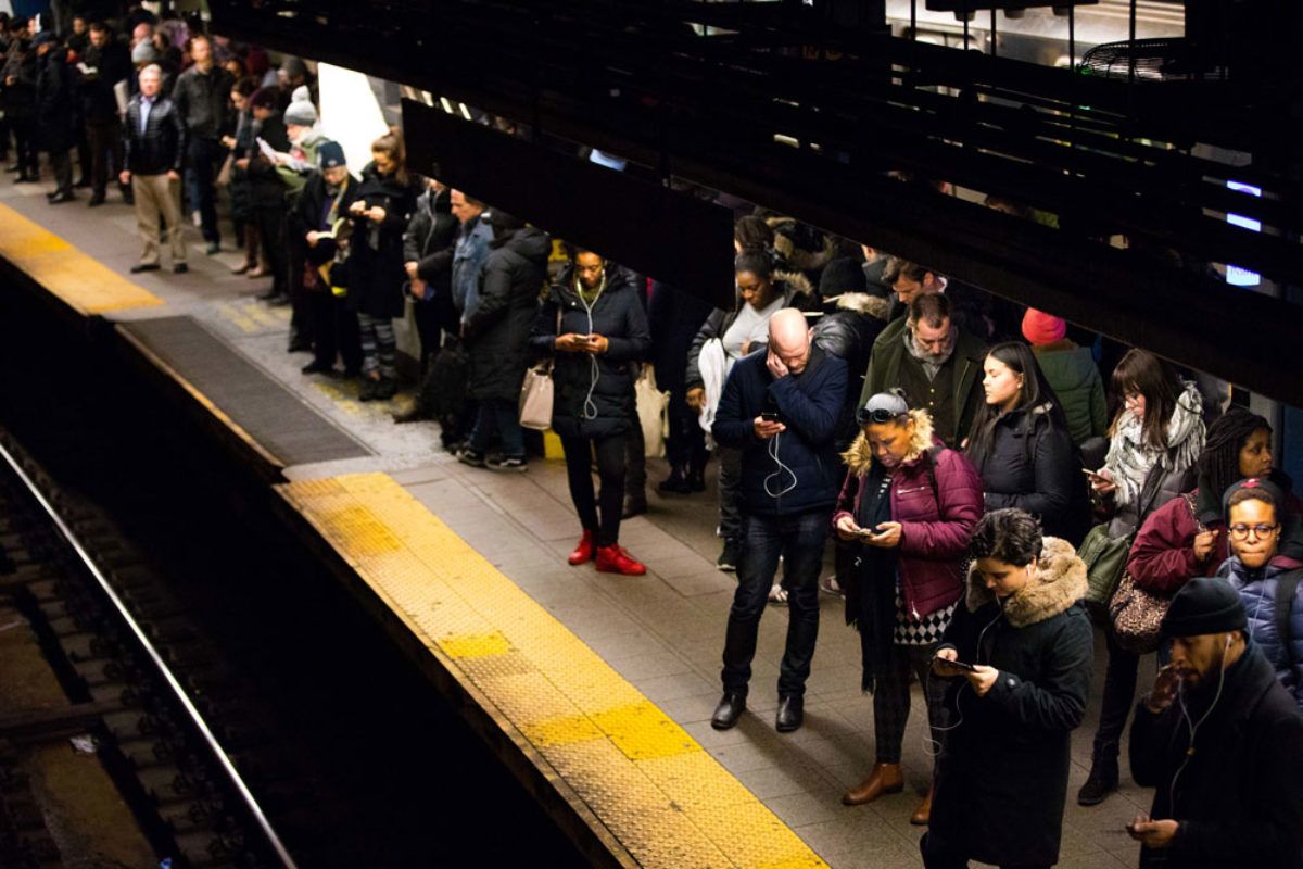 Photograph of people waiting on a platform for a subway in NYC.