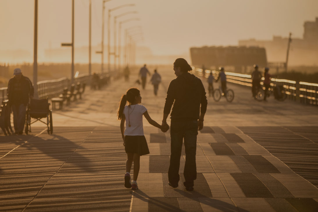 Photograph of people walking on the Coney Island boardwalk at sunset.