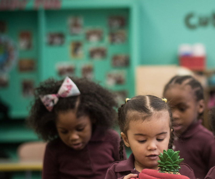 Photograph of a child with a potted plant in a classroom.
