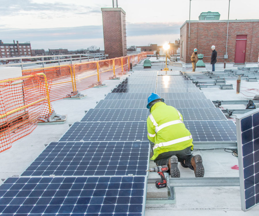 Photograph of construction workers installing solar panels on a roof top in NYC.