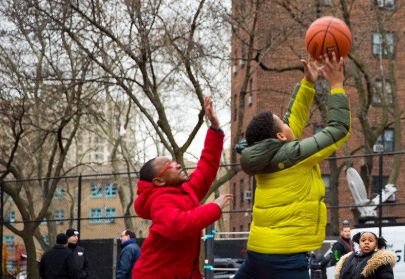 Photograph of children playing basketball in a public park in NYC.